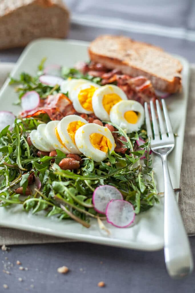 Make a Dandelion Salad with Dandelion greens, Eggs and Bacon for an easy spring dinner! Packed full of vitamins and nutrients! | www.vibrantplate.com