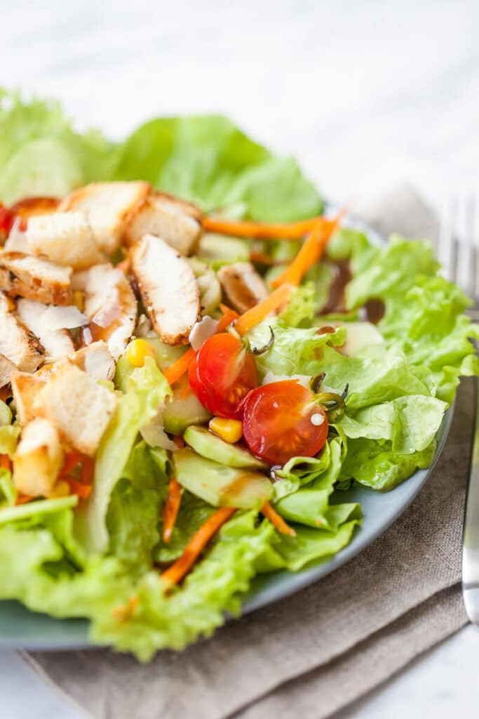 A refreshing and nutritious go-to summer salad with mixed greens, toppings and grilled chicken with balsamic dressing.