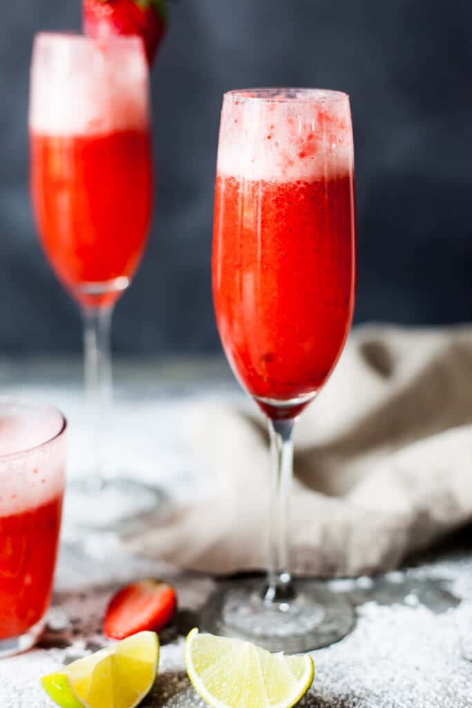 Celebrate Valentine's with this easy & delicious Strawberry Champagne! Mix champagne with strawberry puree for a delightful drink. | www.vibrantplate.com