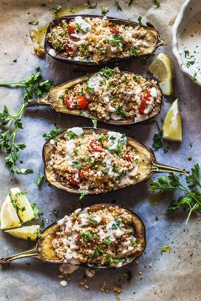 Eggplants stuffed with couscous and topped by lemon tahini sauce. Fresh parsley and lemon slices are spread around them.