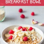 Vegan quinoa breakfast bowl with raspberries on top, pictured from the side.