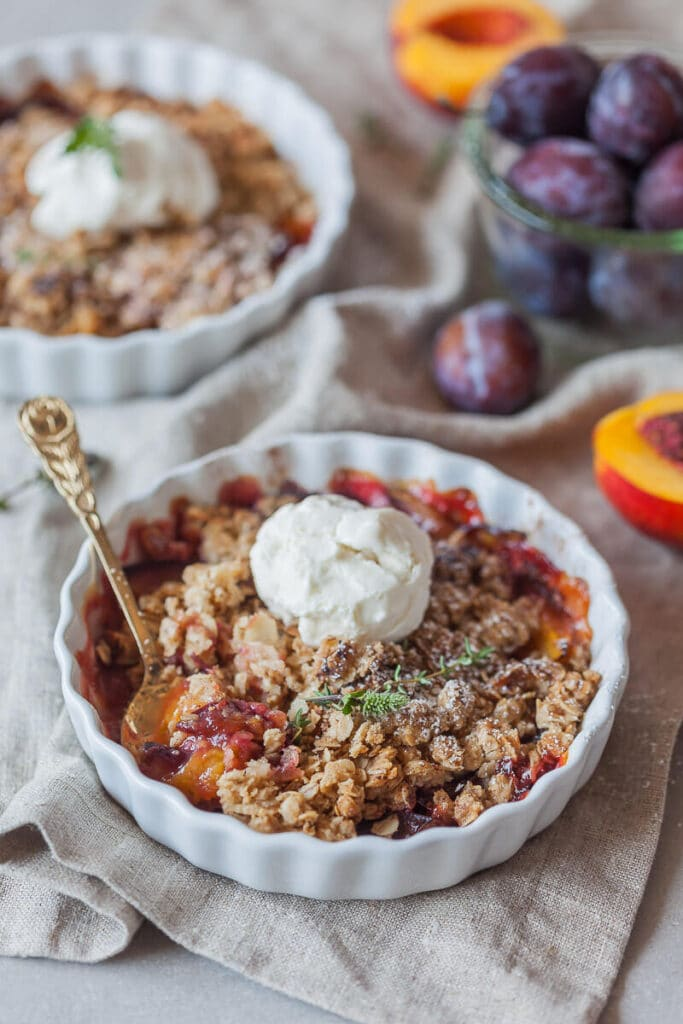 Plum crumble served in a bowl with a scoop of ice cream on top.